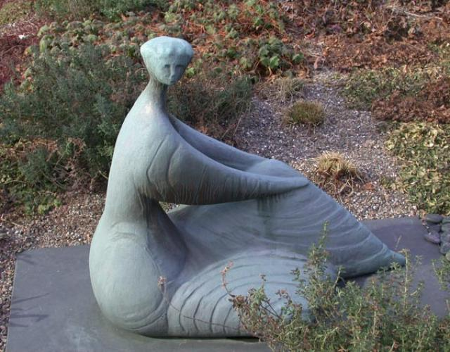 Seated Woman statue surrounded by grass